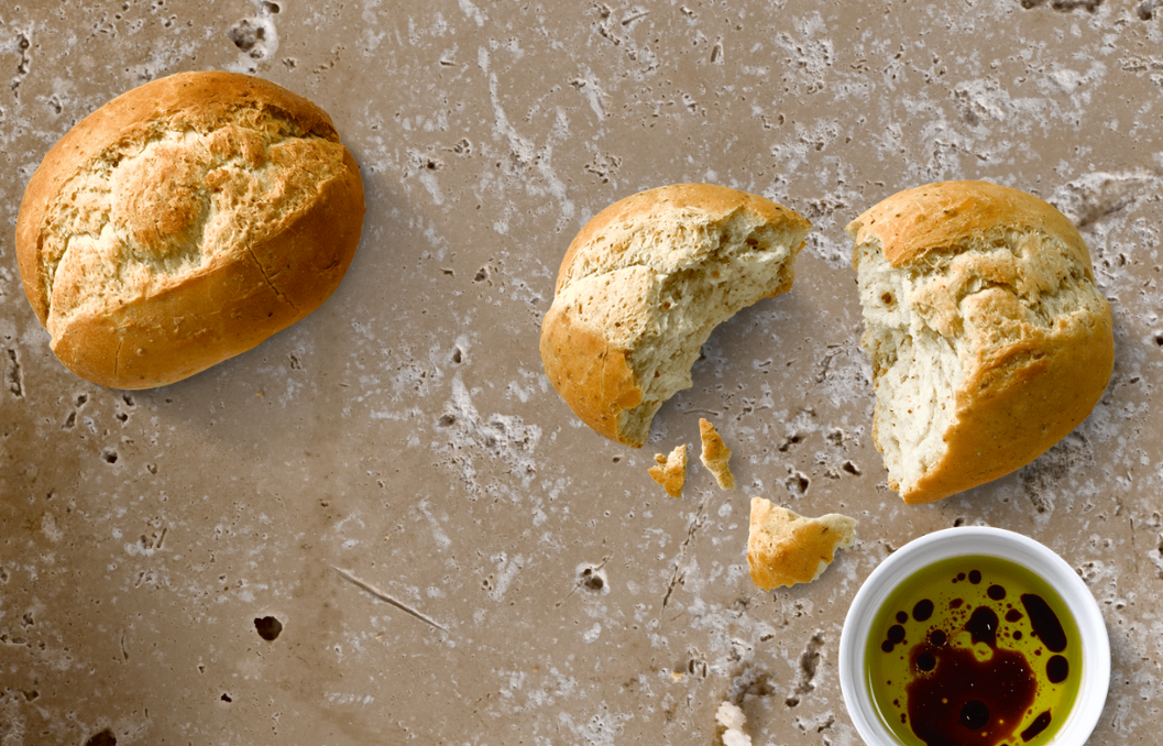 Juvela Part-Baked Rolls with olive oil and balsamic dip against a light stone background