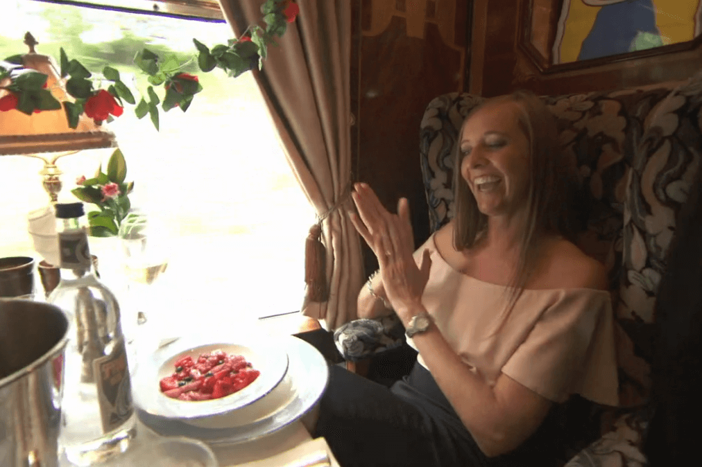 Image of Jemma Rigby on a train during The Apprentice episode, clapping as she receives a fruit salad as a gluten free option
