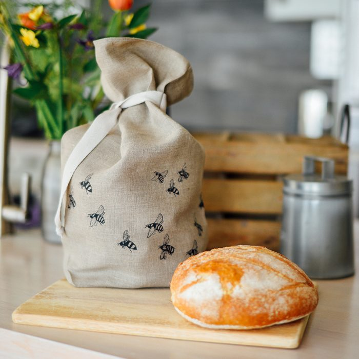 Linen bag with bumblebees print sits next to rustic loaves of bread on a wooden board