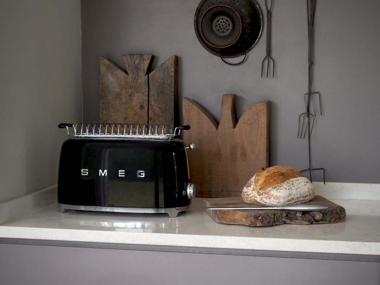 Balck toaster on a worktop with rustic looking bread next to it