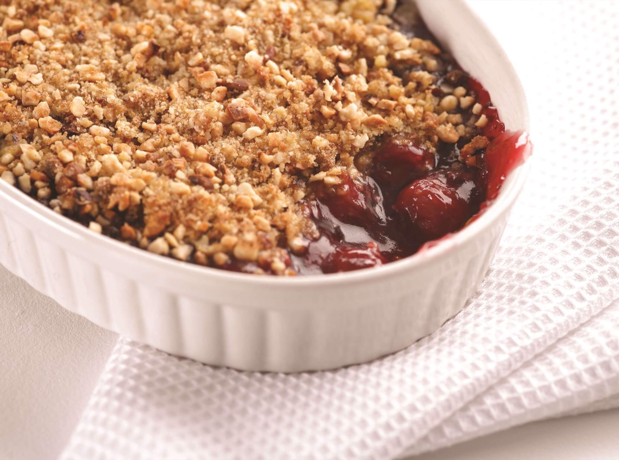 Gluten Free apple and blackberry crumble on a rustic baking tray and tea towel