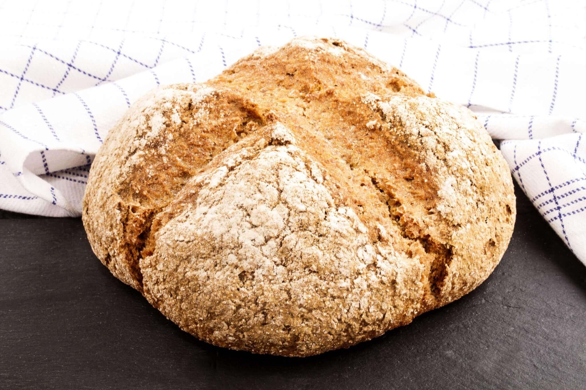 Close up image of a full loaf of soda bread on a white teatowel