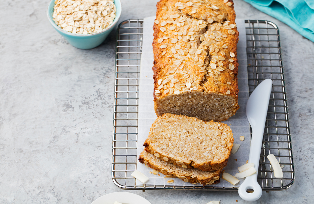 Loaf of porridge bread on a cooling rack, next to a bowl of oats